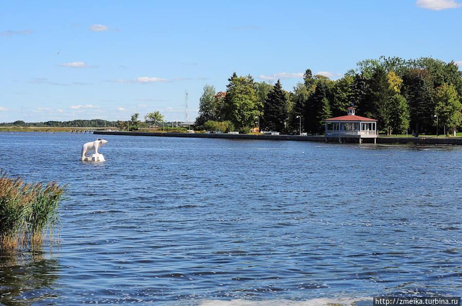 Белый медведь в воде :) Вдалеке беседка на воде.