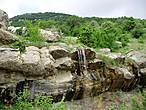 Это немноговодный водопад, искрящийся в лучах солнца. Здесь нет бурных потоков и грохота падающей воды. Он утонченно и возвышенно создает мир гармонии и красоты, подчеркивает святость этого места.
