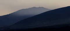 Вид на облысевшие  от кислотных дождей горы и высящийся на них крест.