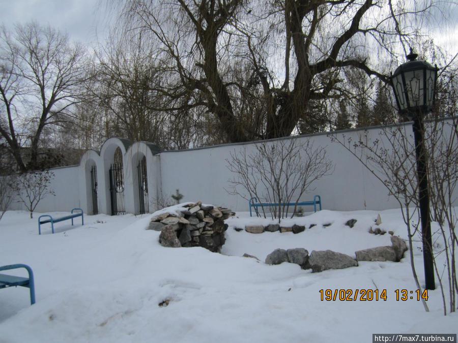 Уютная территория храма. Посажены деревья и сделаны скамейки для отдыха.