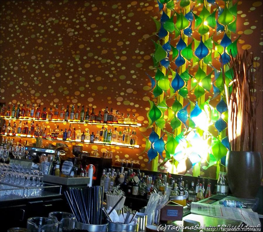 Огромных размеров зеркала, увеличивающие и без того немалое помещение. Окна в два этажа отражаются в зеркале, огромный дверной проём ведёт в музей современного искусства. Зелено-оранжевая раскраска стен выглядит весёленько, как-будто забавлялись тут с мыльными пузырями. Высокий потолок, респектабельная кожаная мебель, огромный светильник и пятнистый дизайн стен – создана великолепная атмосфера минимальными оформительскими средствами.