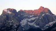 Лучи перекатываются на соседний хребет, окрашивая багрянцем верхушки огромных отвесных скал.