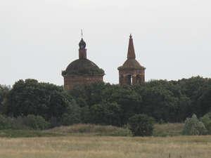 Церковь проглядывает через верхушки деревьев на подъезде к селу.