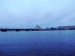 По ту сторону Рижского замка — река Даугава. Вы видите Каменый мост (1957) и Замок Света (Национальная библиотека) на другом берегу.