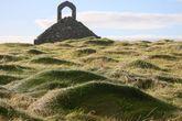 Холмы из сочной травы ведут к кельтско-норманнской часовне Святого Майкла, середины 12 века.