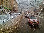 теплый троллейбус растапливает снег на стекле, демонстрируя красивые импрессионистские картины снежно-серого города