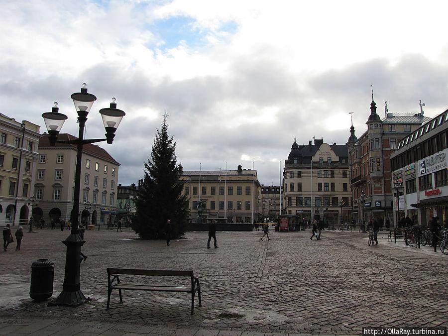 Площадь Stora Torget зимой. Фонтан и скульптура видны за елью.