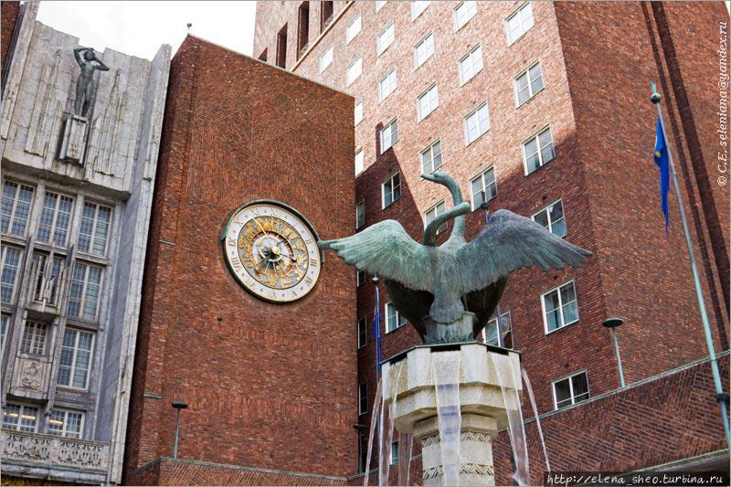 21. На снимке уместилось почти всё, что есть на  северном фасаде и возле него — фонтан с двумя лебедями, астрономические часы, скульптура девушки (разумеется, обнажённой). Это жительница Осло, она приветствует  гостей города.