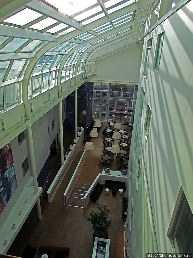 холл, он же ресторан отеля — застекленное светлое помещение на все 4 этажа