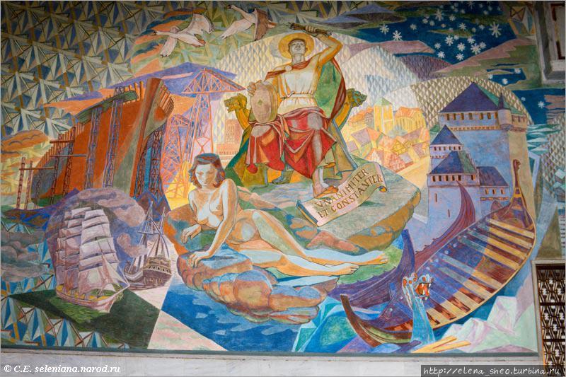 31. Возле лестницы находится очень важная концептуальная фреска, изображающая святого Хальварда — небесного покровителя города Осло. Легенда гласит, что Хальвард пытался спасти от трех разбойников некую женщину, но разбойники пустили в них каждый по стреле и убили обоих. После этого они повесили на шею Хальварду тяжелый жёрнов и бросили его тело в воду, но тело всплыло вместе с жёрновом. Разбойники были уличены, а Хальвард стал святым. Его  изображают с тремя стрелами. Эти три стрелы нередко встречаются и отдельно от Хальварда, в чём мы скоро убедимся, даже не выходя из этого здания. У ног святого можно прочесть девиз города Осло: Unanimiter et constanter (