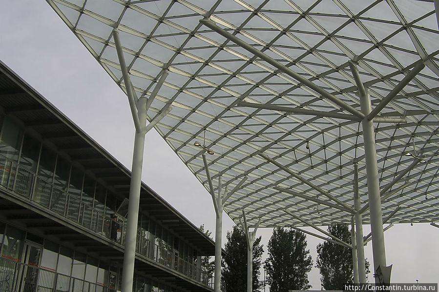 Пространство между павильонами накрывает решетчатое волонообразное покрытие из металла и стекла.