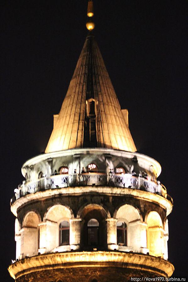 Вид на смотровую площадку Галатской башни с туристами вечером.