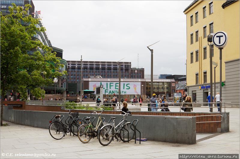 11. Велосипедная стоянка возле входа в метро неподалёку от железнодорожного вокзала, который виден на заднем плане.