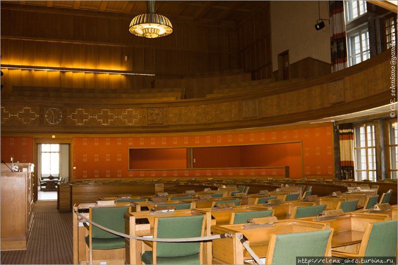 32. Поднимаемся на второй этаж. Здесь находится зал заседаний городского совета (Bystyresalen). Интересно, что даже сюда можно зайти безо всяких проблем. Тут где-то ходит охранник, призванный, видимо, присматривать за этим залом, но в момент съёмки его не было. Во время заседаний сюда тоже можно прийти — на балкон, и оттуда наблюдать, о чём говорят народные избранники. Стены зала обиты красной тканью, на которой выткано изображение трёх стрел. Стрелы уже живут своей жизнью, не зависимой от своего первоисточника — святого Хальварда. Слева от прохода виден край трибуны, где во время заседаний сидит председательствующий и другие лица, причастные к ведению заседания.