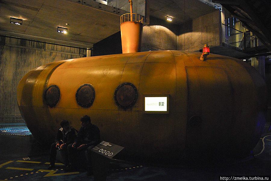 Желтая подводная лодка, на которой каждый 15 минут можно совершить самое короткое в мире путешествие вокруг света)  Внутри лодка похожа на настоящую подводную, В ней расположено три ряда скамеек, на которые садятся пассажиры. В носу лодки установлен большой экран, на котором изображено ее продолжение, и сидит капитан, который и проведет это путешествие)  Интересно, что при