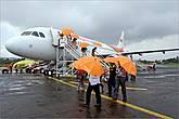*Дождь так и не прекратился, когда самолет приземлился, и нам выдали оранжевые зонтики