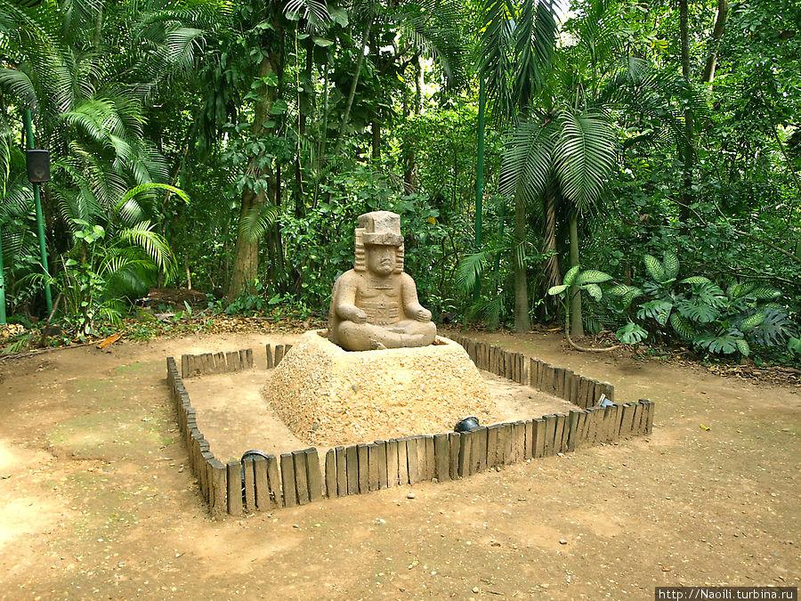 Скульптура правителя, сидящего со скрещенными ногами.