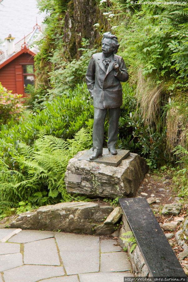 6. Григ был невысокого роста, а в Норвегии почему-то все памятники людям делают натурального размера — ни капли гигантизма. Вот и эта скульптура изобразила человека в его натуральную величину. Мал да удал был великий норвежский композитор Эдвард Григ. На заднем плане виднеется что-то красное, какой-то домик. Мы туда обязательно придём, но не сейчас.