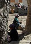 на площади женщины занимались делами по хозяйству, две перетирали перец, остальные стирали