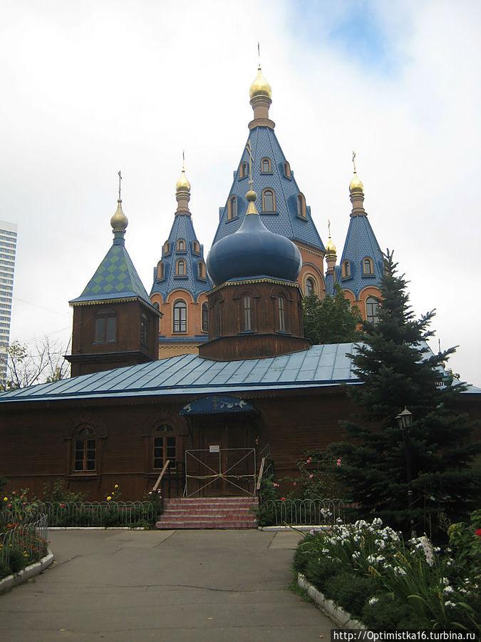 В марте 1997 г. построена деревянная церковь-часовня. Фото сделано 4 сентября 2011. На переднем плане — деревянная церковь, с которой началось возведение храма.