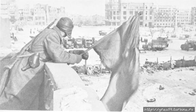 Красный флаг над площадью Павших борцов освобожденного Сталинграда. На заднем плане: здание универмага. На площади: захваченные советскими войсками немецкие грузовики.