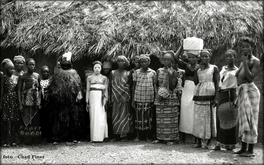Bondo Initiate in White Kaolin at Bitema in Nongowa Chiefdom — 1969. In the center is a young Bondo initiate covered in a white clay during one of the stages of her initiation. To her right is the Bondo Masquerade which was known locally as the Bondo Devil. Location : Bitema Nongowa — Kenema District — Eastern Province Северная провинция, Сьерра-Леоне
