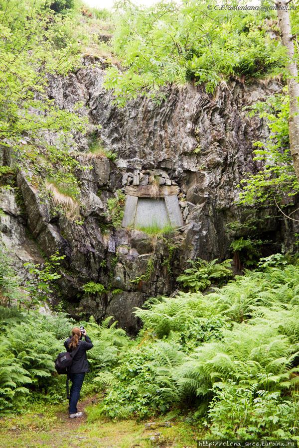 21. Тропа ведёт нас под мостиком, по которому мы ранее  шли к дому Грига, и в конце концов приводит к его могиле. Он похоронен в этой скале неподалёку от своего дома. Вместе с ним покоится его жена Нина, пережившая своего мужа на 28 лет.