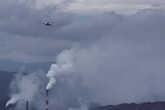 Вертолет пролетает на дымом заводских труб.