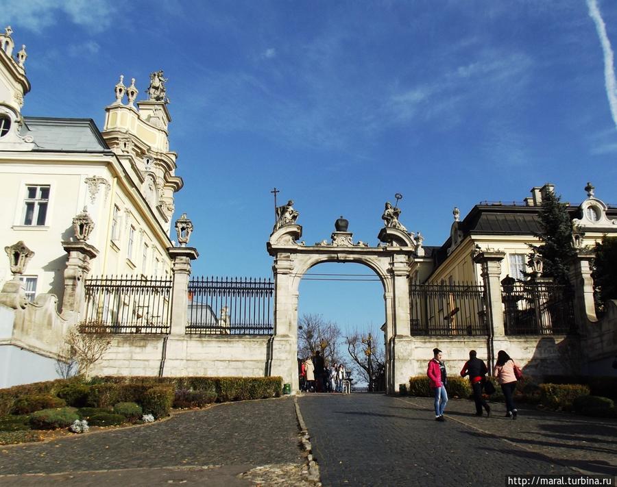 Врата перед храмом украшают аллегорические фигуры — символы Веры и Надежды, Православная Церковь Греции и Римо-католическая Церковь