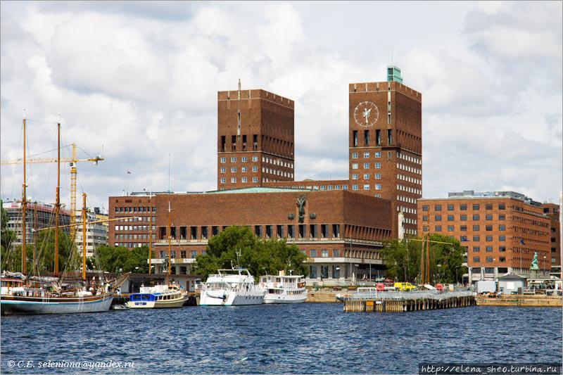 10. Наиболее эффектно она выглядит с одного хорошего мола, который выдаётся в гавань. Красное здание справа зрительно воспринимается как часть ратуши, но на самом деле не имеет к ней никакого отношения. Это просто соседнее здание. У меня есть подозрение, что здания справа и слева от ратуши специально построили в похожем стиле, чтобы усилить впечатление от самой ратуши.