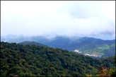 Внизу  виднеется  городок  Бринчанг,  до  него  расстояние  около  трех  км.  хода  по  очень  крутому  склону.  Мы  не  учли,  когда  решились  на  спуск,  того,  что  до  нас  здесь  прошли  сильные  дожди. Было  сыро,  под  ногами  хлюпала  жижа,  вся  тропа  была  перевита  корнями  деревьев  и  лиан. Мне,  в  китайских  сандалиях,  было  скользко  и   неудобно.  Из  Бринчанга   до  своего  городка  Тамах  Рата  мы  вернулись  на  такси.