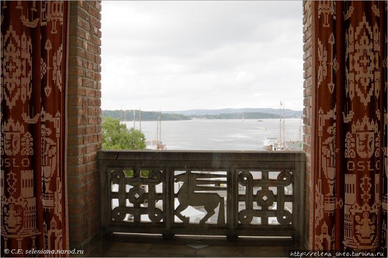 25. А там окна с тяжёлыми бордовыми портьерами и в окнах вид на Осло-фьорд. Небо, увы, закрыто облаками, а потому картина за окном серая, бесцветная.