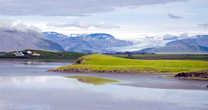 Вдали — ледовая громада Ватнайокюль, самого большого ледника Европы. С нее спускается ледовый язык ледника Hoffellsjökul