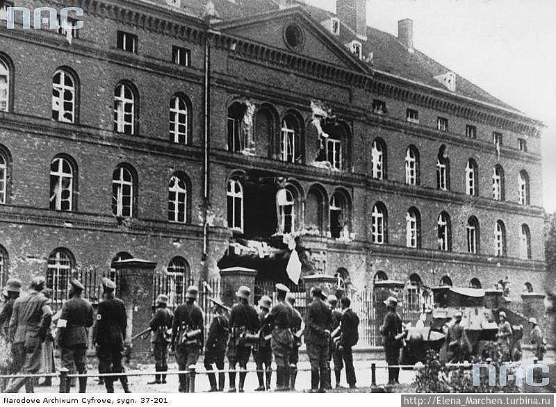 Немецкие солдаты смотрят на разрушенное здание Польской почты.