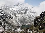Первое маленькое озерцо, которое я увидела, пряталось сперва за облаком, а, когда то улетело, открыв обзор, оказалось, что водоем скрывал огромный камень скалы. Но и этого было достаточно, чтобы открыть рот в изумлении: озеро в заснеженных горах я видела впервые...