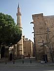 Виден один из минаретов мечети Селимие — бывший собор Святой Софии. Их два и они являются визитной карточкой Никосии. Собор очень старый. Его строительство было начато в 13 веке , а после завоевания Никосии турками в 1571 г. собор Св. Софии превратили в мечеть , надстроив минареты.Она так и называлась — мечеть Айя София и только в 1954 г была переименована в Мечеть Селимие в честь Султана Селима второго , при котором был завоеван Кипр.