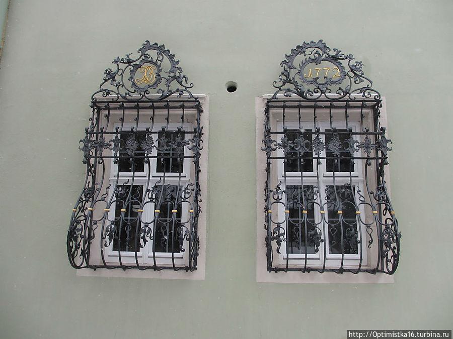 Богато украшенные коваными решётками в стиле барокко окна дома. Решётки изготовлены в 1772 году, сам же дом намного старше.