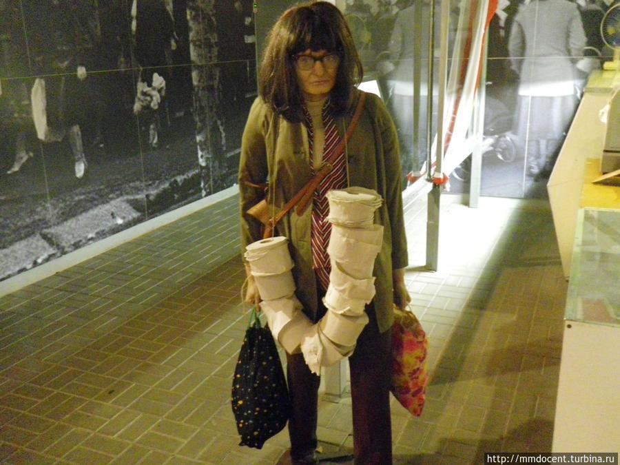Фигура покупательницы, увешанной дефицитной туалетной бумагой.
