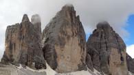 Ну и немного справки. Восточный пик носит название Чима Пиккола (2857 м), «маленькая вершина», центральный – Чима Гранде (2999 м), «большая вершина», а западный – Чима Овест (2973 м), «западная вершина». Как и другие местные горы, они сложены из слоистого доломита.  Вплоть до 1919 года Трэ Чиме ди Лаваредо служили частью естественной границы между Австрией и Италией, а сегодня они разделяют итальянские провинции Больцано и Беллуно и все еще служат «лингвистической» границей между немецко- и итало-говорящими этническими группами. Первое задокументированное восхождение на Чима Гранде состоялось в августе 1869 года – его предпринял австрийский писатель и любитель гор Пол Грохманн в сопровождении проводников Франца Иннеркофлера и Петера Сальчера. Чима Овест была покорена десять лет спустя – в августе 1879 года, а Чима Пиккола – только в 1881 году. На две последние вершины взошел Майкл Иннеркофлер. Те тропы, которыми шли первопроходцы, существуют и по сей день. Дорога на вершину Чима Пиккола считается самой сложной из трех, а северный склон Чима Гранде, покоренный только в 1933 году, входит в шестерку так называемых «великих северных склонов Альп».