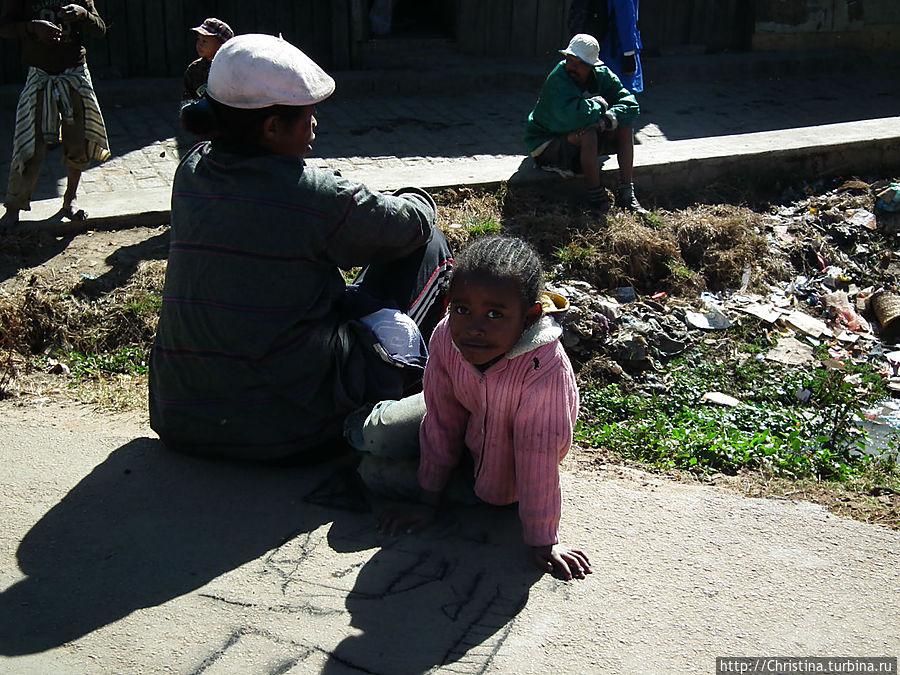 Дети, люди, нищие, отдыхающие и просто кто-угодно еще — все сидят на тротуарах и на обочине дороги. Антананариву, Мадагаскар