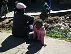 Дети, люди, нищие, отдыхающие и просто кто-угодно еще — все сидят на тротуарах и на обочине дороги.