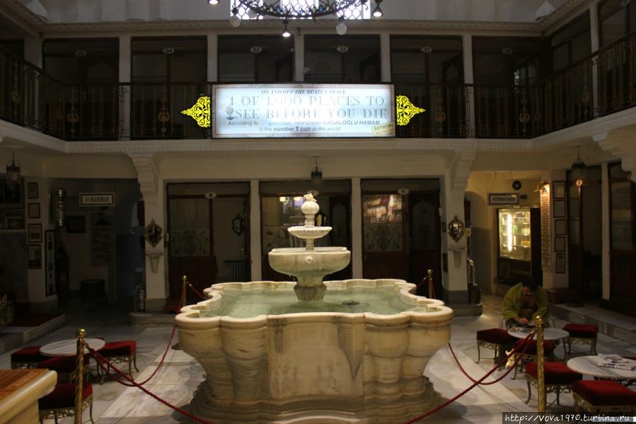 Зал с фонтаном и банщик в ожидании клиентов.