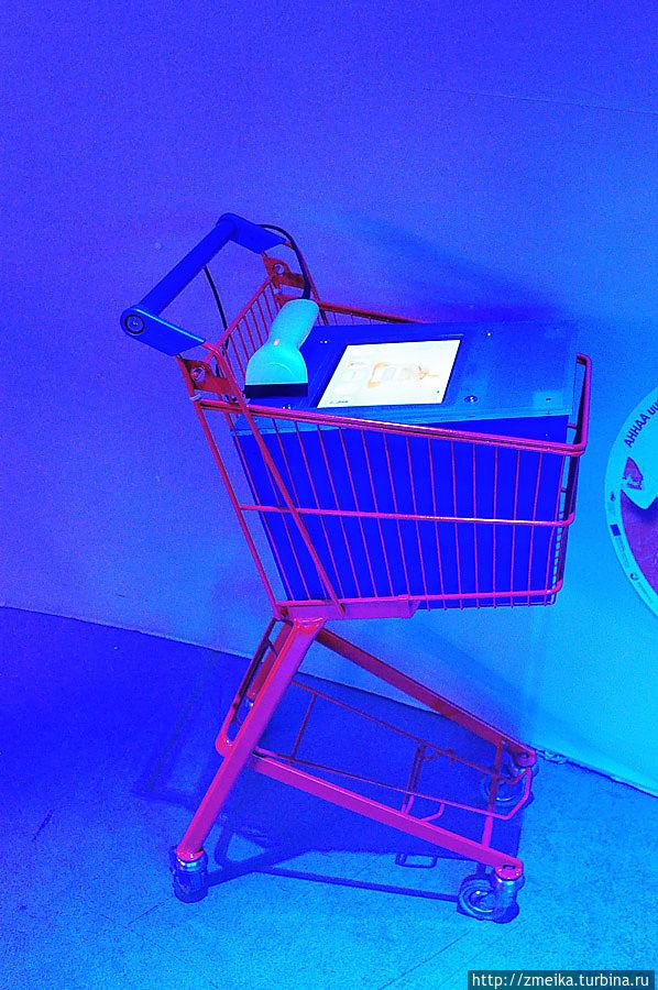 Электронная тележка с ручным сканером и экраном, на котором показывается, что уже есть в телеге