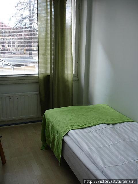 Кровать в номере и маленькая шторка на окне