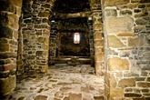 Вход в храм закрыт железной решеткой, но через нее просматривается каменный зал храма, у противоположной стены виднеется каменная купель и лежащий за ней крест.