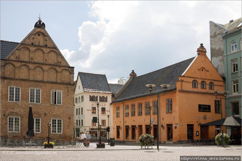 7. Слева самое старинное здание Осло — так называемый дом Ратмана (Rådmannsgården), построенный в 1626 году. Что такое или кто такой Ратман, никому не известно. Вроде бы Ратман — это не фамилия, а должность, так называли выборного члена магистрата. По норвежской транскрипции я бы скорее сказала, что это дом Родмана. Теперь в доме располагается ассоциация художников Осло. Справа в здании приятного апельсинового цвета с 1641 по 1733 годы располагалась ратуша. По этой причине его называют Старой ратушей в отличие от новой современной ратуши, с которой мы уже познакомились. После ратуши в здании был Верховный суд, а теперь находятся Театральный музей и ресторан. Между домом Ратмана и Старой ратушей через площадь идёт улица Rådhusgata. Глядя на это весьма и весьма небольшое здание, невольно удивляешься, что в нём когда-то смогла уместиться вся городская власть. Теперь-то в нём вряд ли уместился бы даже самый маленький отдел мэрии. Впрочем, сейчас город несравнимо больше того, какой был три века назад.