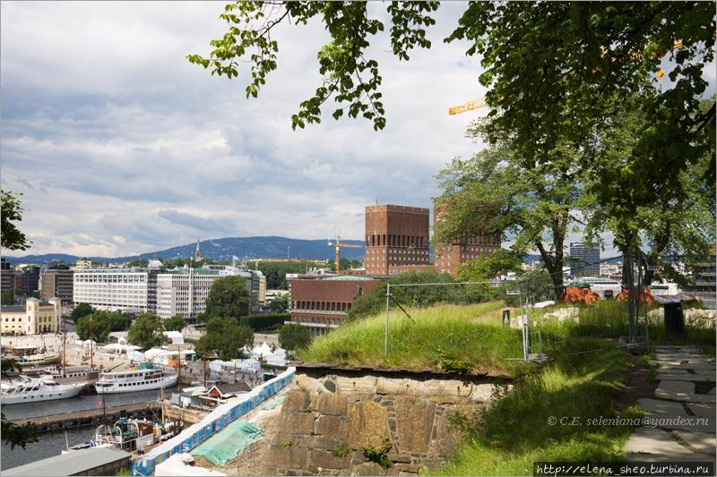 9. На переднем плане часть крепостной стены, за ней видна ратуша. На горе, виднеющейся на горизонте, если приглядеться, можно увидеть  трамплин Холменколлен (Holmenkollen), одну из достопримечательностей Осло.