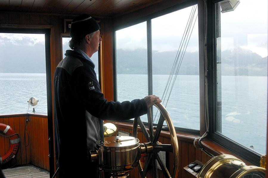 Рулевой за штурвалом парохода