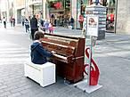 ... а другой тем, как сумел вытащить пианино на пешеходную зону. Хоть музыкант достаточно юный, но не забыл спрятать за музыкальным инструментом полиэтиленовый чехол на случай дождя.