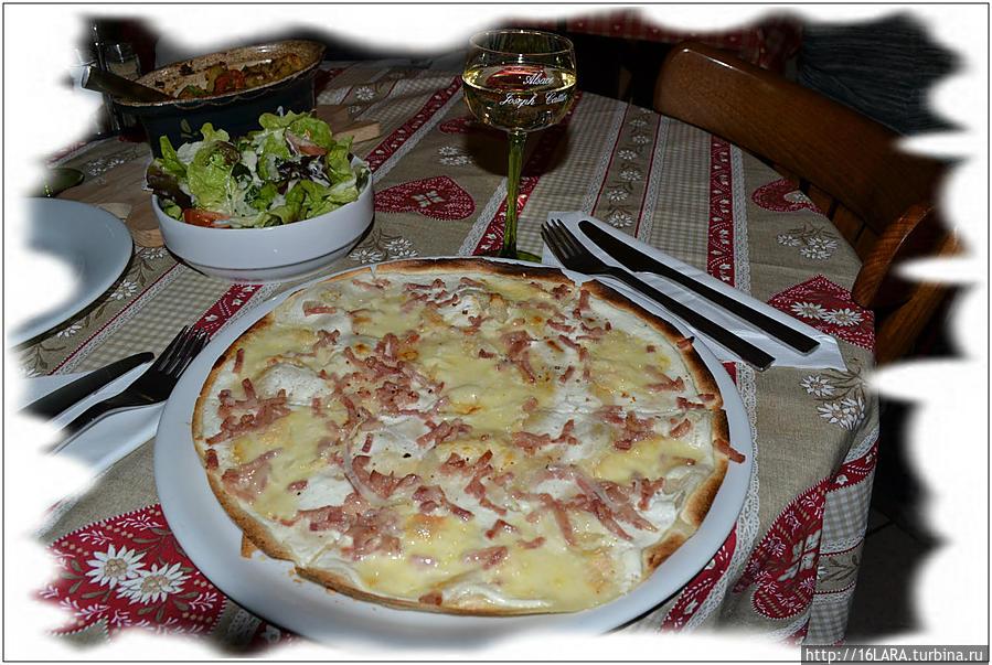 Тарт фламбе или иначе Мюнстерский пирог — это что-то вроде пиццы, но не пицца. К нему вино Гевюрцераминер  в прозрачном бокале на зеленой ножке — тоже традиция. Сыр мюнстр — это довольно